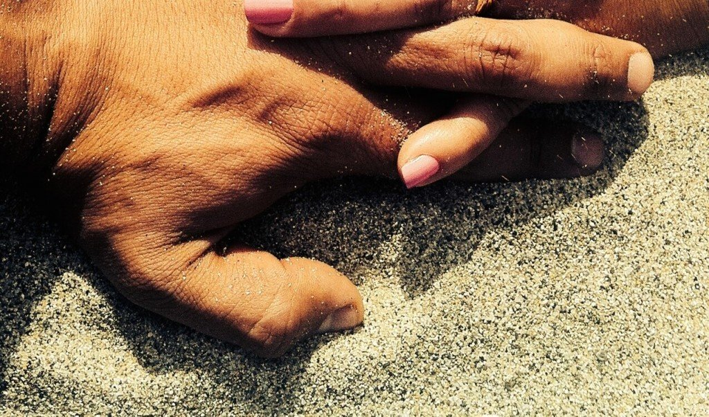 Couple hands in sand
