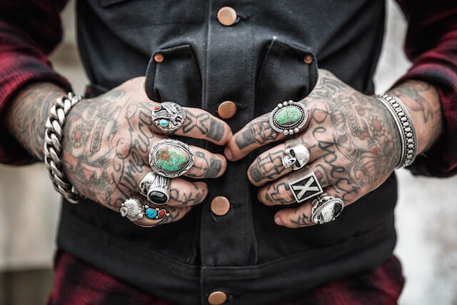 Tattooed hands with rings