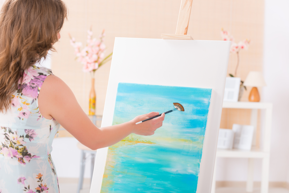 A woman working on a painting.