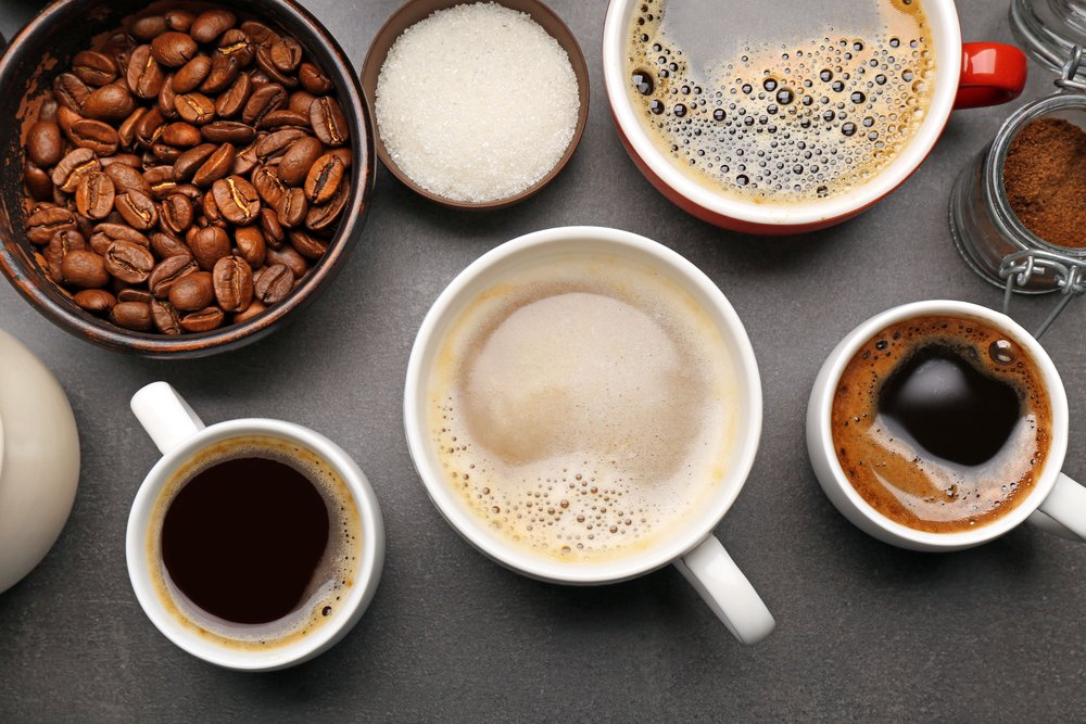 A variety of coffee cups on a dark table