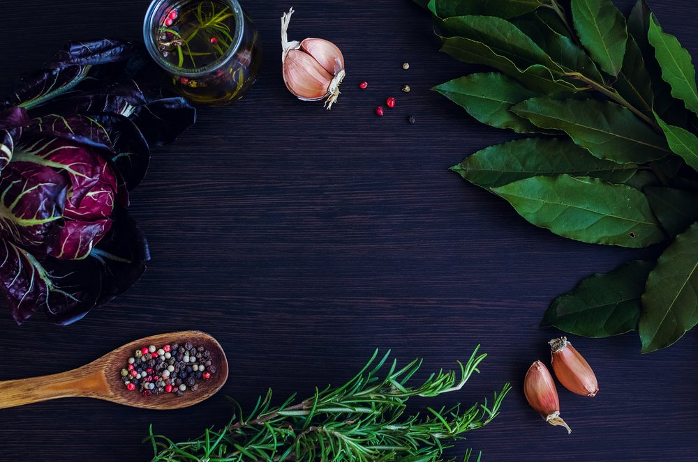 Garlic, chicory, rosemary, and bay leaves on a dark-colored table