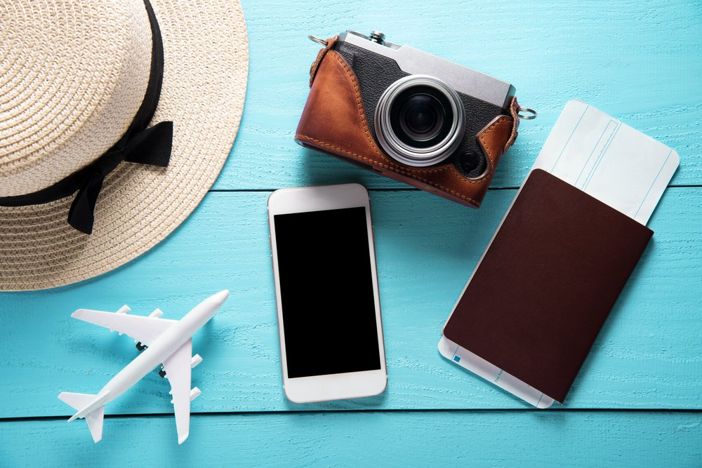 Phone, camera, hat, passport, and plane figurine on bright blue background